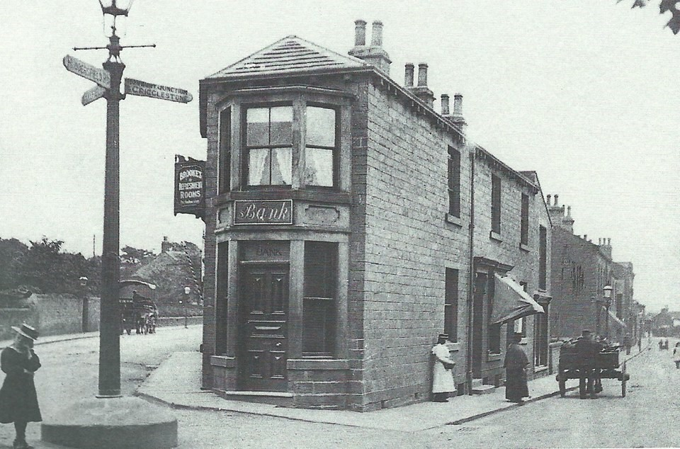 A late 19th century black & white image showing the building as a bank, with a sign for